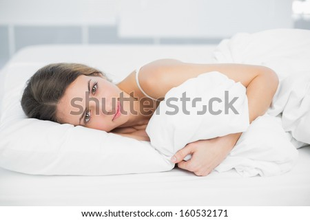 Attractive calm woman lying on her bed holding her cover looking at camera