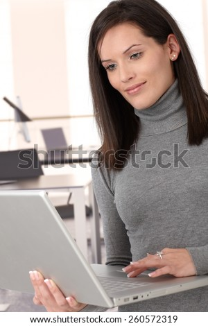 Attractive casual caucasian brunette secretary working with laptop computer - stock photo