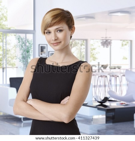 Attractive casual caucasian young businesswoman at designer home, standing, arms crossed, smiling, looking at camera. - stock photo
