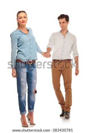 attractive casual couple walking in isolated studio background holding hands. woman is looking at the camera while man is looking at her.  - stock photo