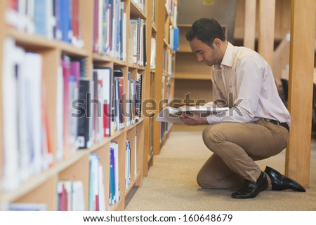 Attractive casual man reading a book in library kneeling in front of bookshelves
