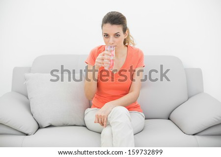 Attractive casual woman drinking a glass of water looking at camera sitting on a sofa - stock photo