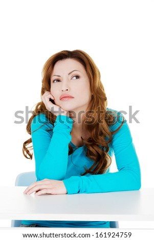 Attractive casual woman propping her head and looking up. Isolated on white.  - stock photo