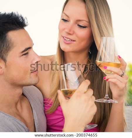 Attractive casual young couple drinking a glass of wine in a hotel terrace. - stock photo