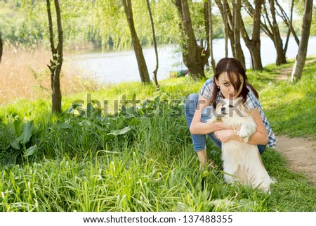 Attractive casual young woman bending down and cuddling her tiny dog as they take a walk though the peaceful lush countryside - stock photo