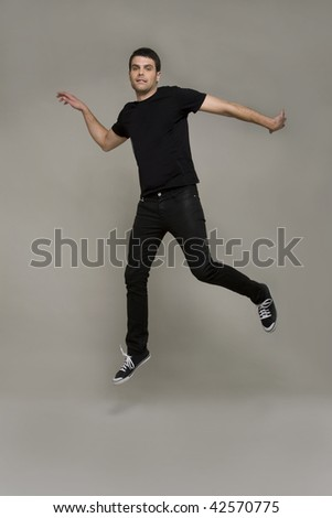 Attractive casually dressed young man caught in the air