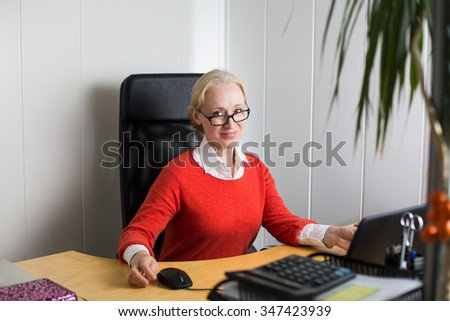 Attractive caucasian blonde business woman working in the office - stock photo