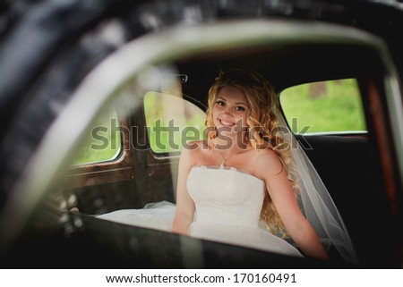 attractive caucasian bride sitting in car and smile to the camera - stock photo