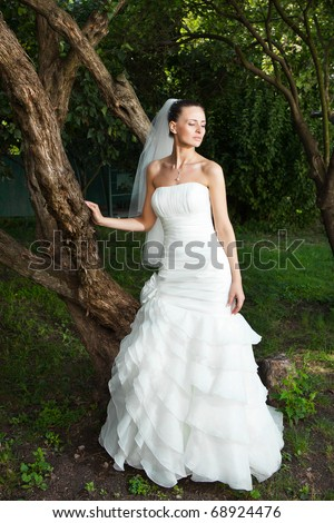 attractive caucasian bride standing near old tree in beautiful dress - stock photo