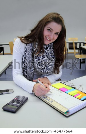 Attractive Caucasian Brunette studying with calculator and notepad, smiling into the camera - stock photo