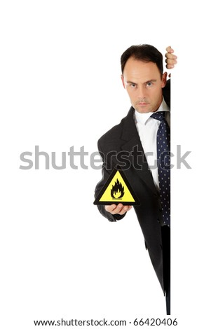 """Attractive caucasian businessman behind wall showing warning sign """"flammable goods"""". Copy space. Studio shot. White background. - stock photo"""