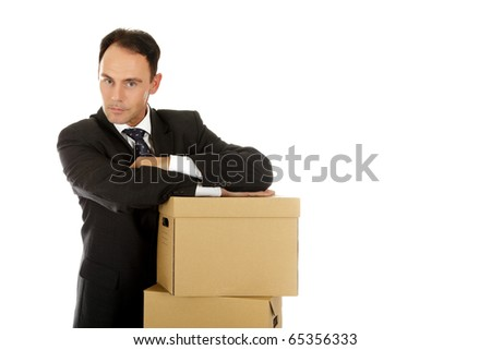 Attractive caucasian businessman in office behind the storage boxes with the hands against them . Studio shot. White background.
