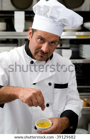Attractive Caucasian chef adding spices to his food