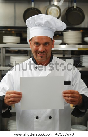 Attractive Caucasian chef holding a blank sign in a commercial kitchen - stock photo