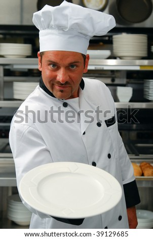Attractive Caucasian chef holding an empty plate in a commercial kitchen - stock photo