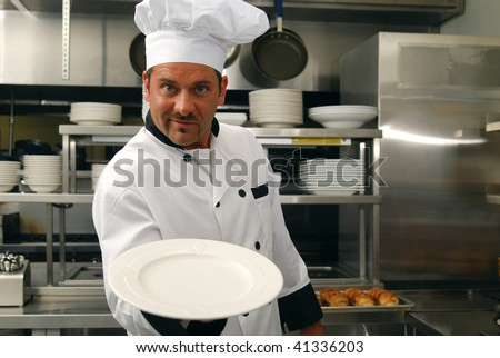 Attractive Caucasian chef holding an empty plate in a restaurant kitchen. - stock photo