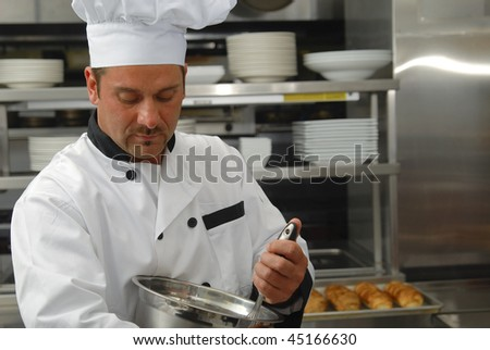 Attractive Caucasian chef mixing food in a bowl in a restaurant kitchen. - stock photo