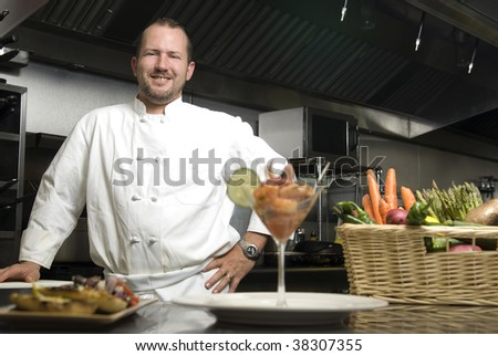 Attractive Caucasian chef standing in a restaurant kitchen with a basket of vegetables.
