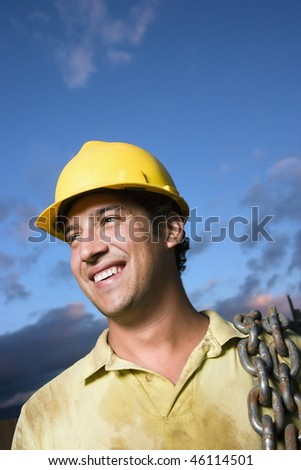 Attractive Caucasian construction worker in a yellow hardhat carries a heavy chain over his shoulder while smiling to the side. Vertical shot. - stock photo