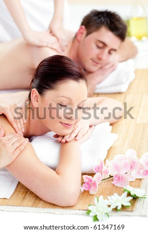 Attractive caucasian couple having a back massage in a spa center - stock photo