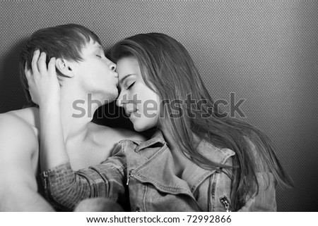 attractive caucasian couple hugs and kisses - stock photo