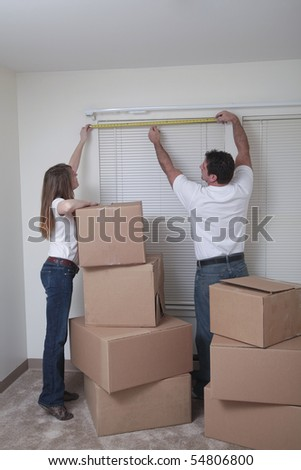 Attractive Caucasian couple measuring the window in their new house.