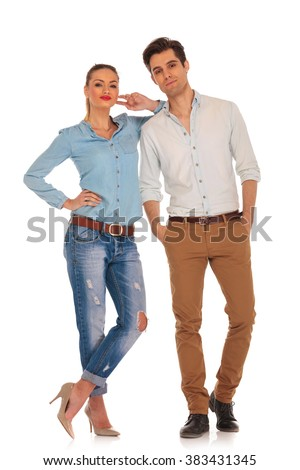attractive caucasian couple posing in white isolated studio background looking at the camera. man has both hands in pockets and woman rests her arm on his sholder with legs crossed