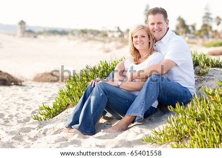 Attractive Caucasian Couple Relaxing and Enjoying the Beach Together. - stock photo