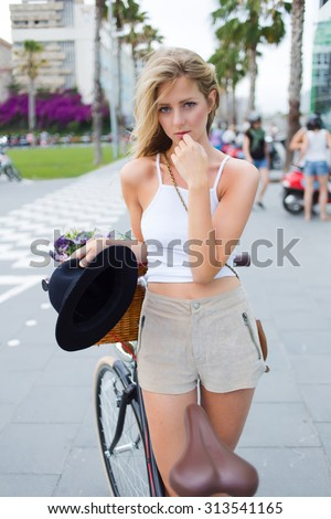Attractive caucasian female with a charming look rest after riding on her retro bike through the streets of the city during weekend,tempting gorgeous young woman standing with classic bicycle outdoors - stock photo