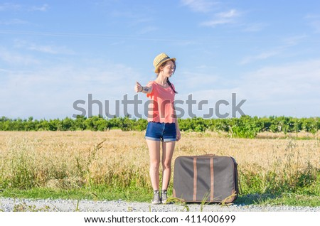 Attractive caucasian girl doing hitchhiking in the countryside - stock photo
