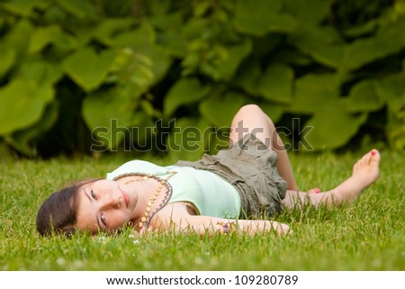 Attractive caucasian girl lying down on her back at the green lawn - stock photo