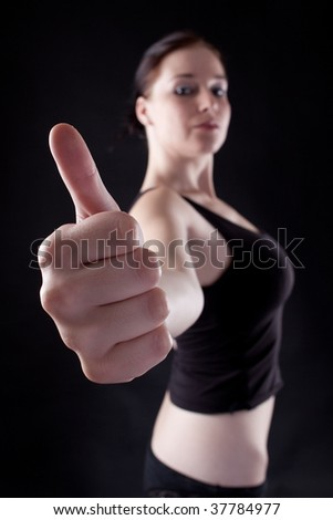 Attractive caucasian girl showing thumbs up. Image isolated on black background - stock photo