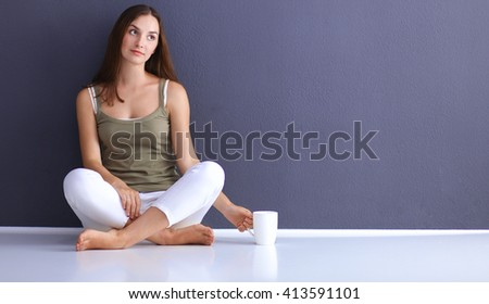 Attractive caucasian girl sitting on floor with phone - stock photo