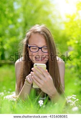 Attractive caucasian girl with a smartphone in the grass - stock photo