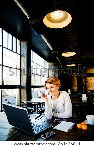 Attractive caucasian girl with red short hair wearing in white sweater sitting in cafe, looking at laptop, holding a pen and smiling, notebook, on the table, big windows at the background - stock photo