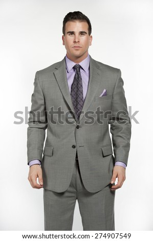 Attractive caucasian male fitness model wearing a trendy fitted and fashionable gray suit with a purple shirt and tie underneath posing in a studio on a white background while looking at the camera. - stock photo