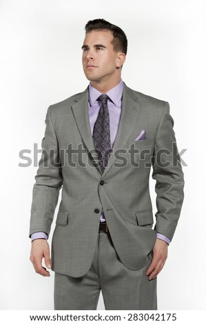 Attractive caucasian male fitness model wearing a trendy fitted and fashionable gray suit with a purple shirt and tie underneath posing in a studio on a white background while looking to the left. - stock photo