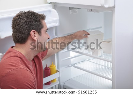 Attractive Caucasian male reaching into a sparse refrigerator - stock photo
