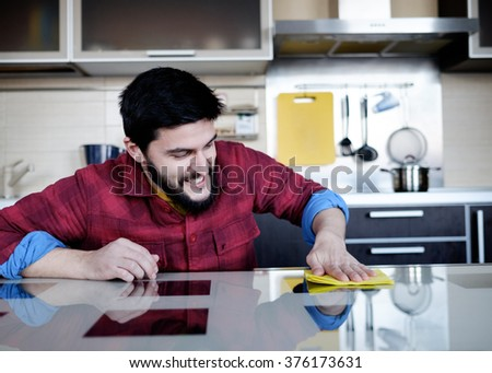 Attractive caucasian man cleaning the table in the kitchen - stock photo