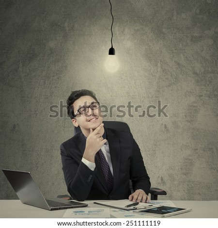 Attractive caucasian manager working on desk and smiling happy while looking at bright lightbulb - stock photo