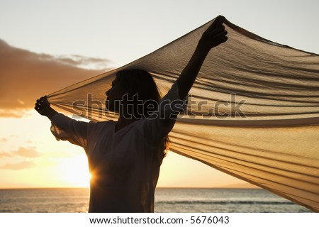 Attractive Caucasian mid-adult woman holding up fabric in breeze silhouetted by sunset beside ocean. - stock photo