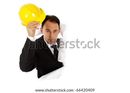 Attractive caucasian middle aged businessman breaking through a paper wall, holding an yellow protective helmet. Studio shot. White background - stock photo