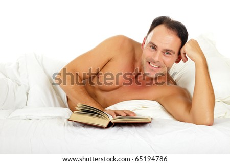 Attractive caucasian middle aged man in  bed reading a book. Studio shot. White background - stock photo