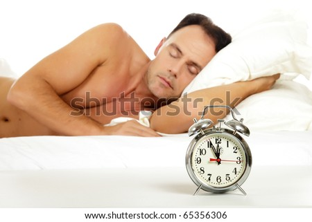 Attractive caucasian middle aged man sleeping and a retro alarm clock showing midnight. Focus on clock. Studio shot. White background. - stock photo