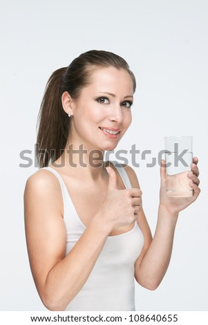 attractive caucasian smiling woman isolated on white studio shot drinking water with thumb-up - stock photo