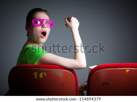 Attractive caucasian woman in the theatre in her 30 isolated on a grey background