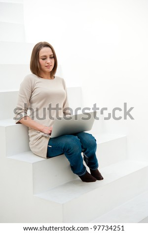 attractive caucasian woman using laptop computer sitting on the stairs