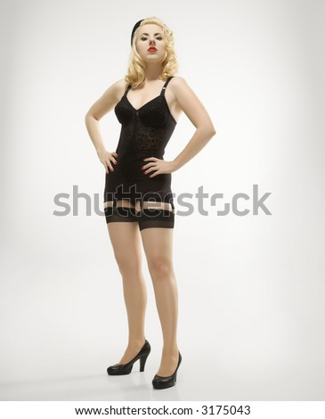 Attractive Caucasian woman wearing retro lingerie in pinup pose.