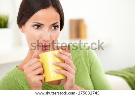 Attractive caucasian woman with pulled back hair blowing on hot coffee while looking away - stock photo