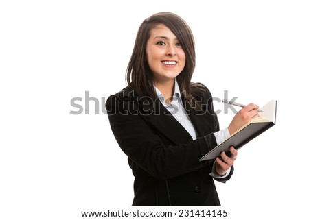 Attractive cheerful assistant writing in notebook - stock photo